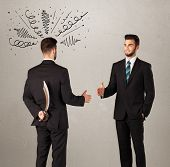 foto of backstabbers  - Ruthless businessman handshake with a hiding weapon and drawn curly lines around his head  - JPG