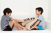 stock photo of pillow-fight  - Little sibling boy playing pillow fighting on sofa - JPG