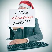 stock photo of office party  - a man sitting in his desk with a santa hat holding a signboard with the text office christmas party written in it - JPG
