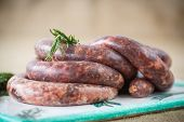 pic of raw chicken sausage  - home hepatic raw sausage with rosemary on a table - JPG