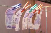stock photo of pesos  - Mexican paper currency of 1000 pesos attached by pins on clothesline to dry in the sun - JPG