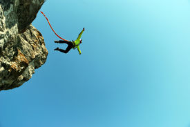 stock photo of roping  - Jump off a cliff with a rope - JPG