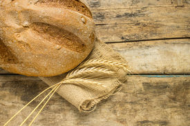 stock photo of husbandry  - Fresh bread with wheat ears on wooden table - JPG