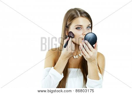 young beautiful woman applying powder on cheek with brush - isolated