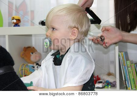 Blonde Little boy cut their hair in a childrens hairdresser, two years baby boy