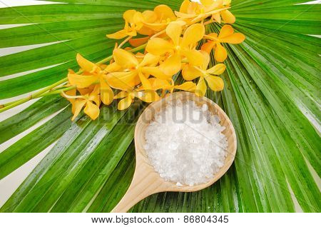 spa setting with yellow orchid and salt in spoon