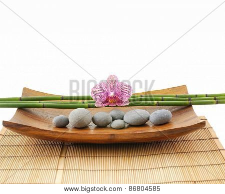 Pink orchid with bamboo grove and stones in bowl on mat texture