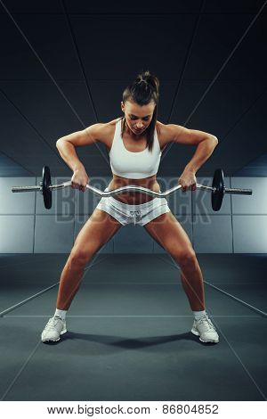 Young Woman Exercising With Barbell And Weights