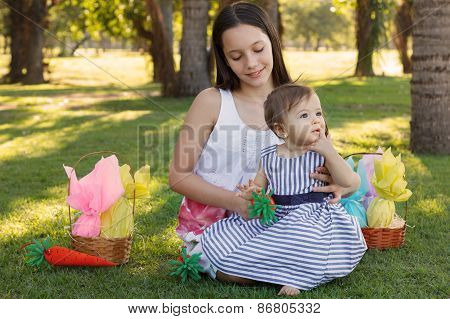 Two Girls Sisters: Baby And Teen With Easter Chocolate Eggs