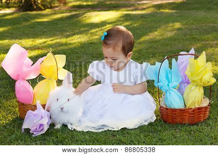 Cute Little Baby Girl In White Dress Touching Rabbit, Easter Chocolate Eggs