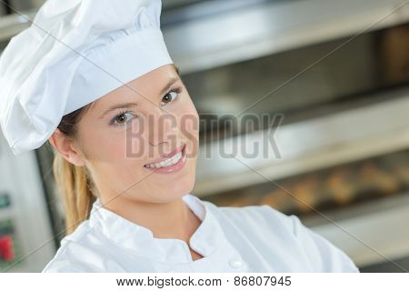 Female baker stood by bread oven