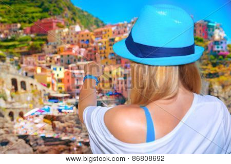 Back side of young girl enjoying beautiful cityscape, Europe, Italy, Cinque Terre, traditional old architecture, buildings painted in different colours