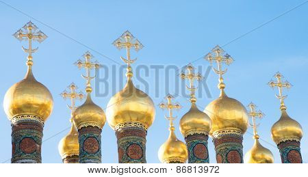 Several gilded domes against the sky.