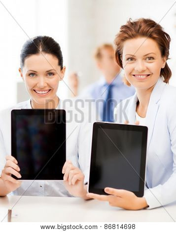 smiling business team showing tablet pcs in office