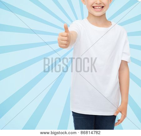 advertising, people and childhood concept - close up of smiling little boy in white blank t-shirt showing thumbs up over blue burst rays background