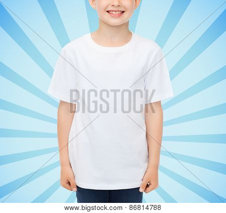 advertising, people, childhood and t-shirt design concept - smiling little boy in white blank t-shirt over blue burst rays background