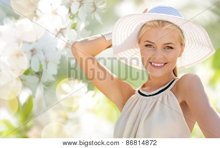 fashion, people and summer holidays concept - beautiful woman in hat and dress over green blooming garden background
