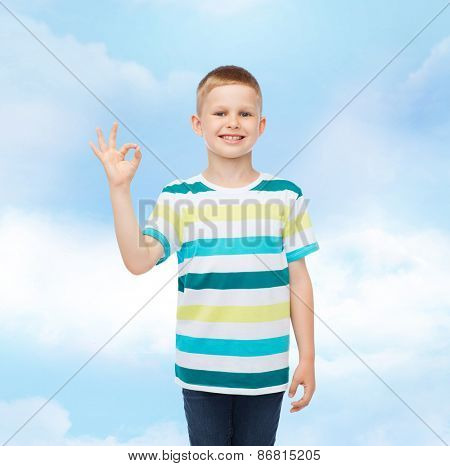 childhood, gesture and people concept - smiling little boy in casual clothes making ok gesture over cloudy background