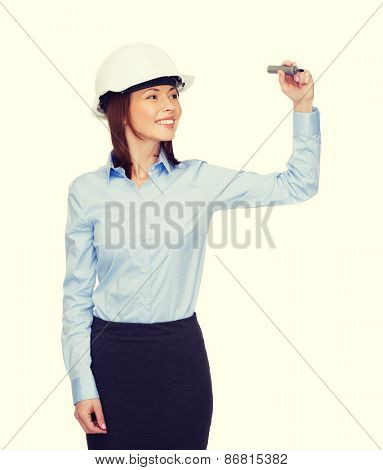 building, developing, consrtuction and architecture concept - smiling businesswoman in white helmet writing something on virtual screen