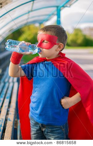 Superhero Standing And Drinking Water From A Bottle