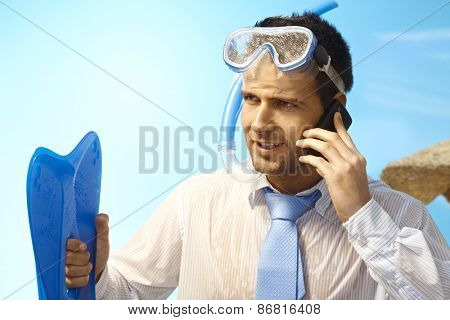 Ambitious young businessman talking on mobilephone on summer holiday.