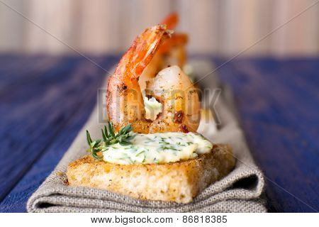 Appetizer canape with shrimp on napkin on table close up