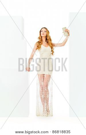 Full length portrait of a gorgeous young woman with long hair posing in beautiful white dress. Fashion shot. Isolated over white.
