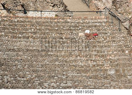 Woman Seated Alone At The Amphitheater Of The Three Gauls In Lyon, France