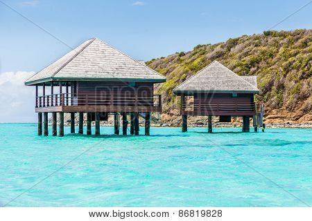 Two Buildings On Stilts Above Tropical Water