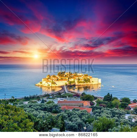 Fantastic view of the Sveti Stefan, small islet and resort in Montenegro. Dramatic morning light. Overcast red sky. Balkans, Adriatic sea, Europe. Beauty world.