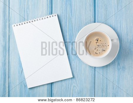 Coffee cup and blank notepad over blue wooden table. Top view with copy space