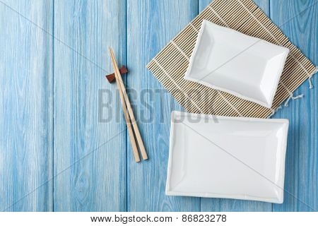 Empty plates and chopsticks on blue wooden background. Top view with copy space