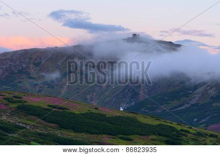 Old observatory on Mount. Mountains in the clouds. Summer landscape. Carpathians, Ukraine, Europe