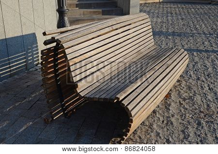 Wooden bench on the pavement