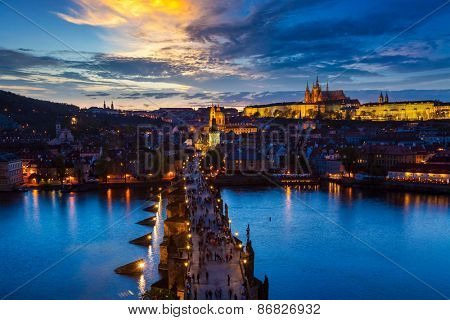 Aerial view of illuminated Prague castle and Charles Bridge with tourist crowd over Vltava river in Prague, Czech Republic. Prague, Czech Republic in the evening