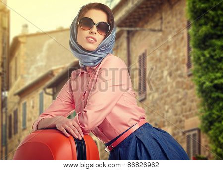 Elegant woman with a suitcase travel on street of italian city