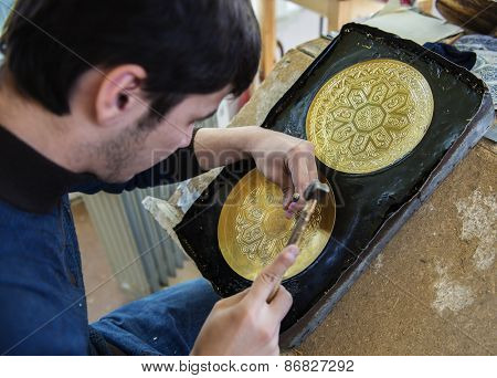 BUKHARA, UZBEKISTAN - MARCH 14, 2015: Young craftsman produces chased dish