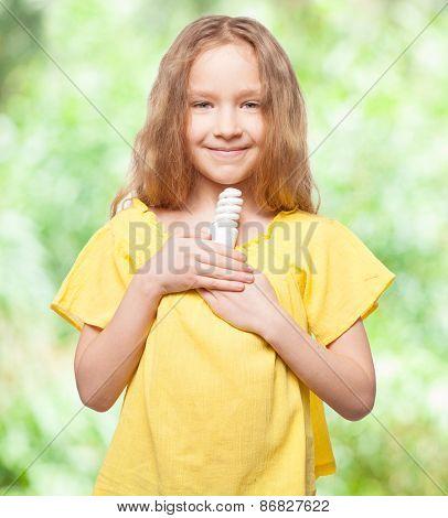 Child with bulb. Girl holding an energy saving lamp