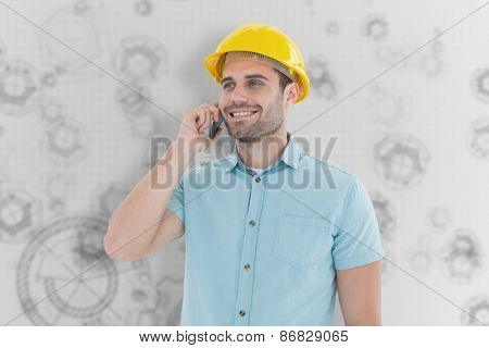 Happy male architect conversing on mobile phone against architect background