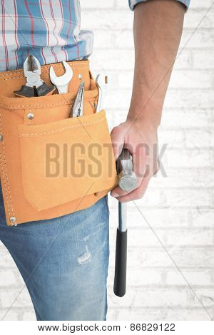 Handyman wearing tool belt while holding hammer against white wall