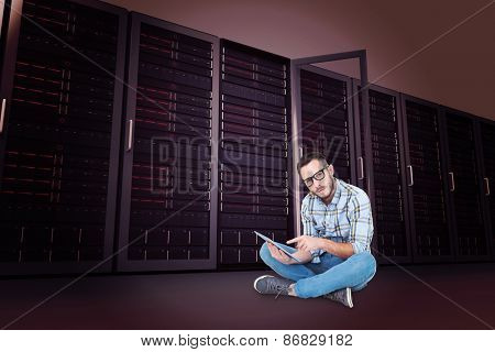 Handsome hipster using tablet pc against server towers