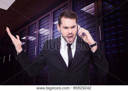 Angry businessman gesturing on the phone against digitally generated server room with towers