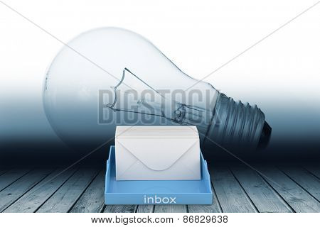 Blue inbox against giant light bulb in room