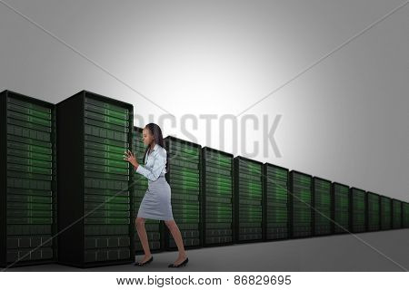 Portrait of a young businesswoman pushing a panel against server tower