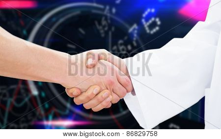 Closeup of a doctor and patient shaking hands against stocks and shares