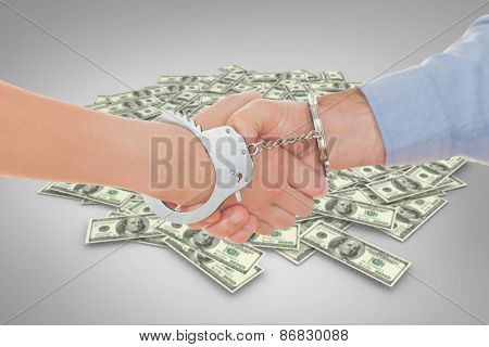 Handcuffed business people shaking hands against pile of dollars