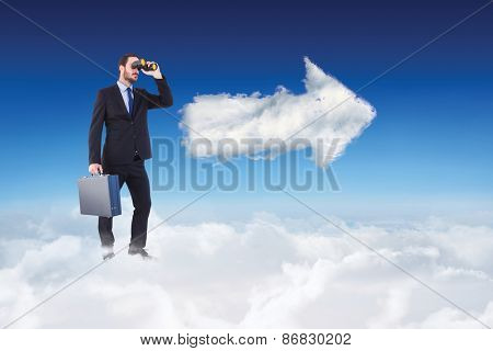 Businessman looking through binoculars holding briefcase against cloud arrow
