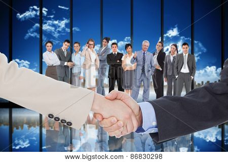 Smiling business people shaking hands while looking at the camera against room with large window looking on city skyline