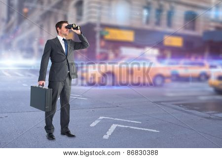 Businessman looking through binoculars against blurred new york street