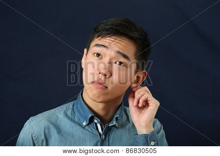 Romantic young Asian man holding his ear and looking upward